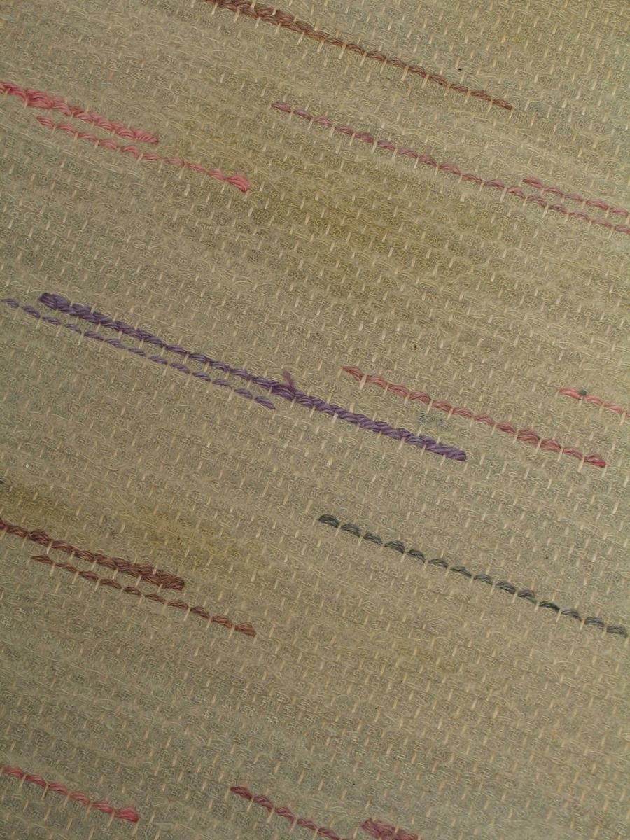 Maskinvevd rye i bomull. Den har bunnfarge i beige med innslag av brunt, rosa, lilla og grønt. To deler med ulik lengde er sydd sammen tilpasset rommet.