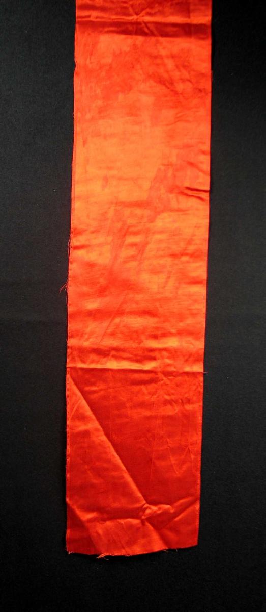 Begravelsessløyfe i rød silke uten tekst.