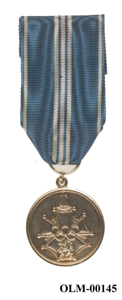 Sølvfarget medalje med blått og hvitt bånd. Medaljen er dekorert med de olympiske ringene og motiv av en løve.