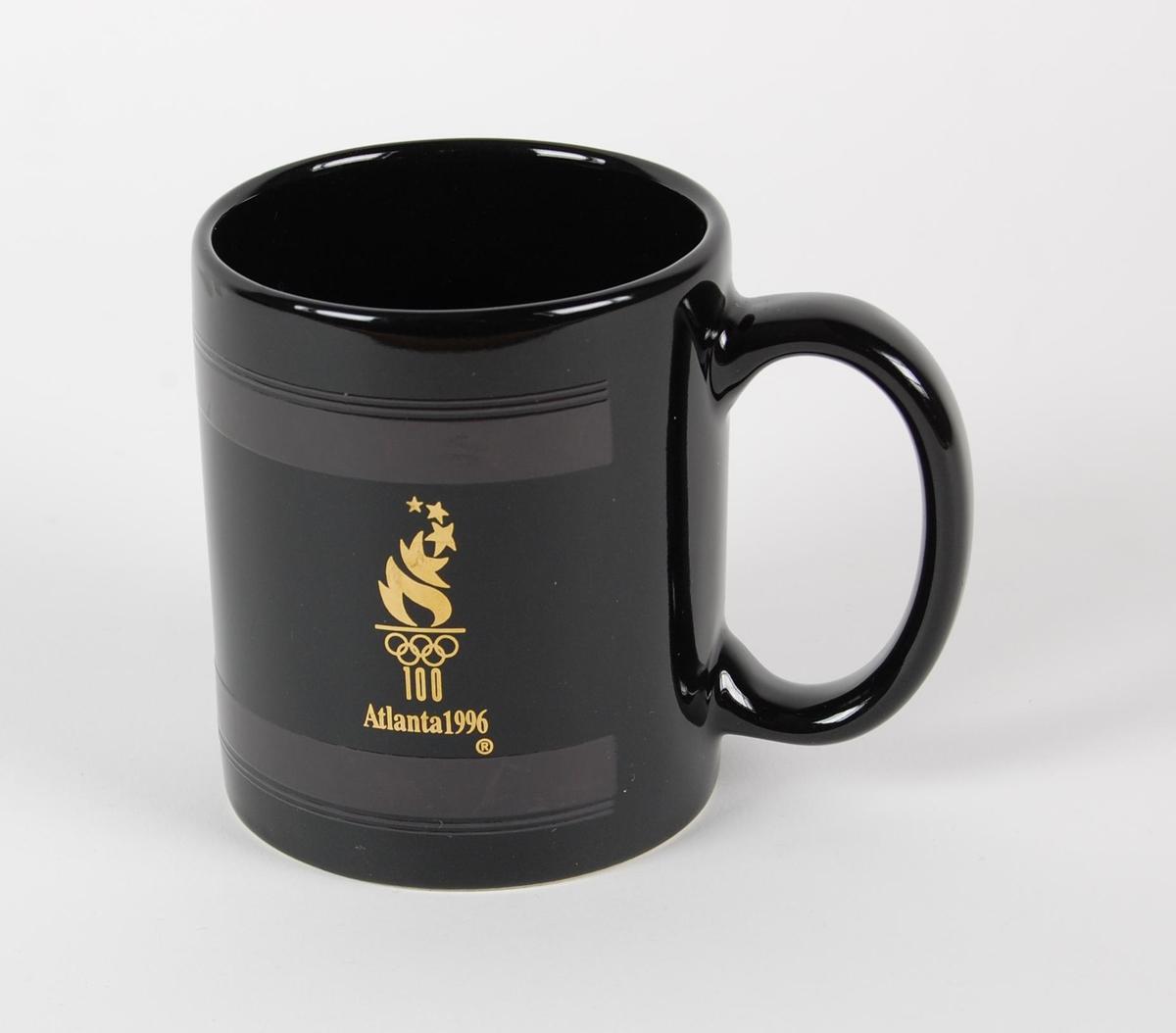 Sort kopp med hank. To gullfarvede logoer. Det er blant annet en logo for de olympiske leker i Atlanta i 1996.