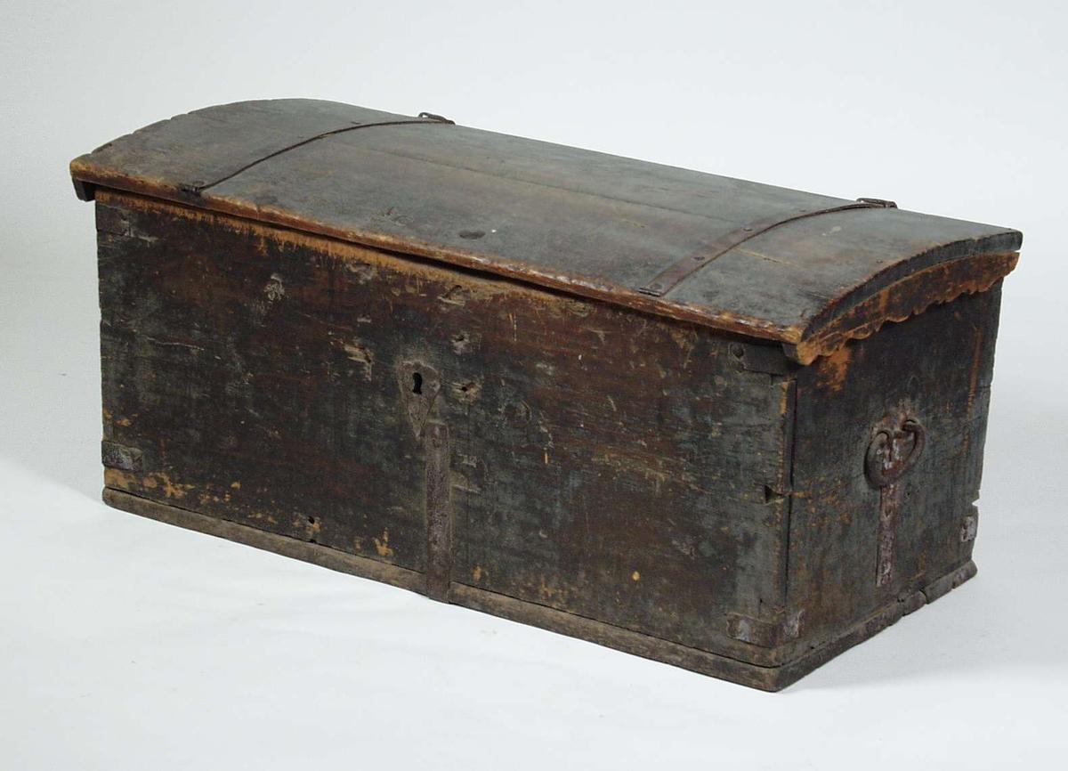 En brun kiste i furu med jernlister på lokket. Kisten er blitt malt to ganger etter at den ble laget. Den har utskjæringer på kantene av lokket og C-formede håndtak. Innvendig på lokket er det pålimt aviser.