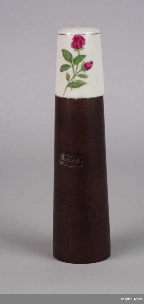 Saltbøsse i mørkt tre.Toppen er i keramikk dekorert med en rose.