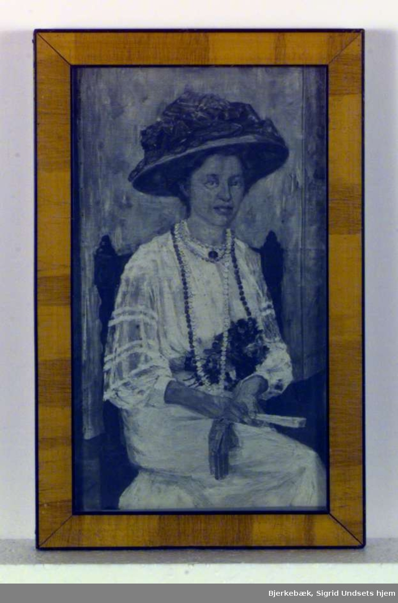 Portrett av sittende kvinne. Kvinnen er iført hvit kjole og stor hatt. Hun har blomster i fanget og lange kjeder rundt halsen.