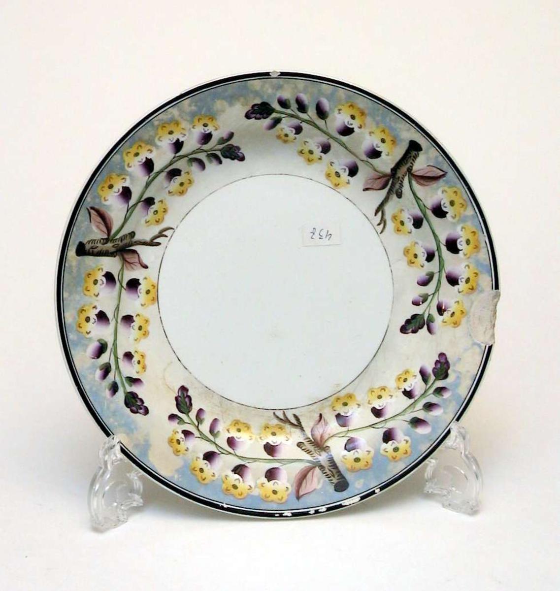 Tallerken i kremfarget keramikk med blomsterdekor i lilla og gult på blå-grå bakgrunn. Det er slått et stort skår av kanten på tallerkenen og den har flere små hakk.