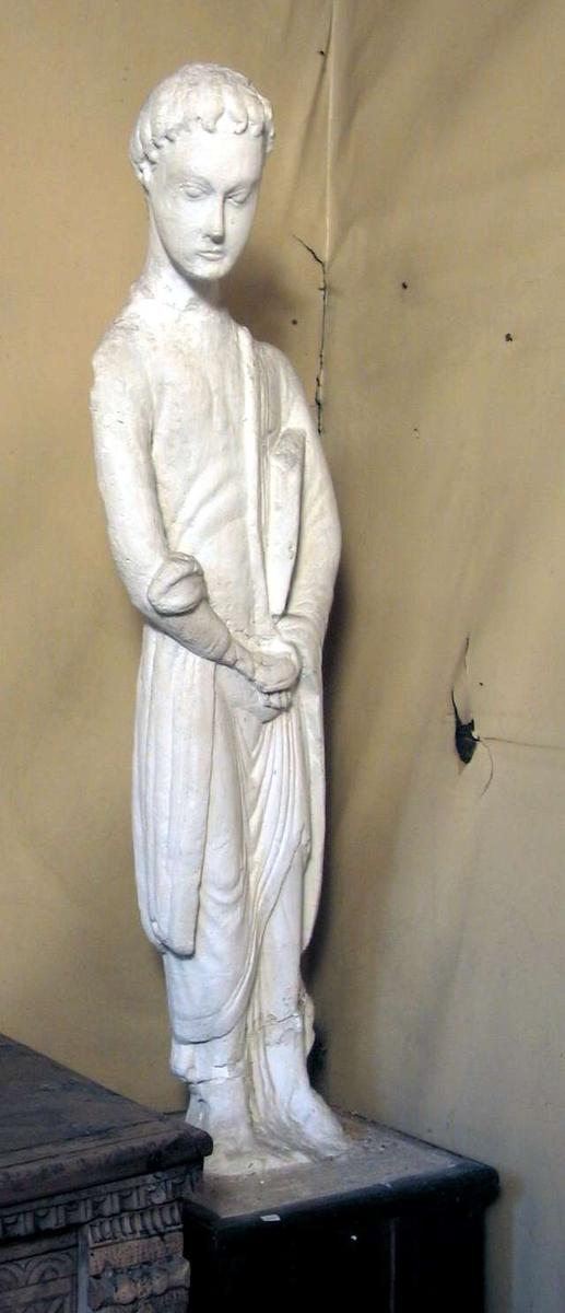 En avstøpning i gips av en treskulptur av evangelisten Johannes. Skulpturen står på en sokkel kledd med tre.