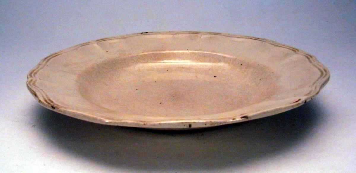 Elfenbensfarget, dyp tallerken. Den har rifler langs kanten.  Det er skår i glasuren.