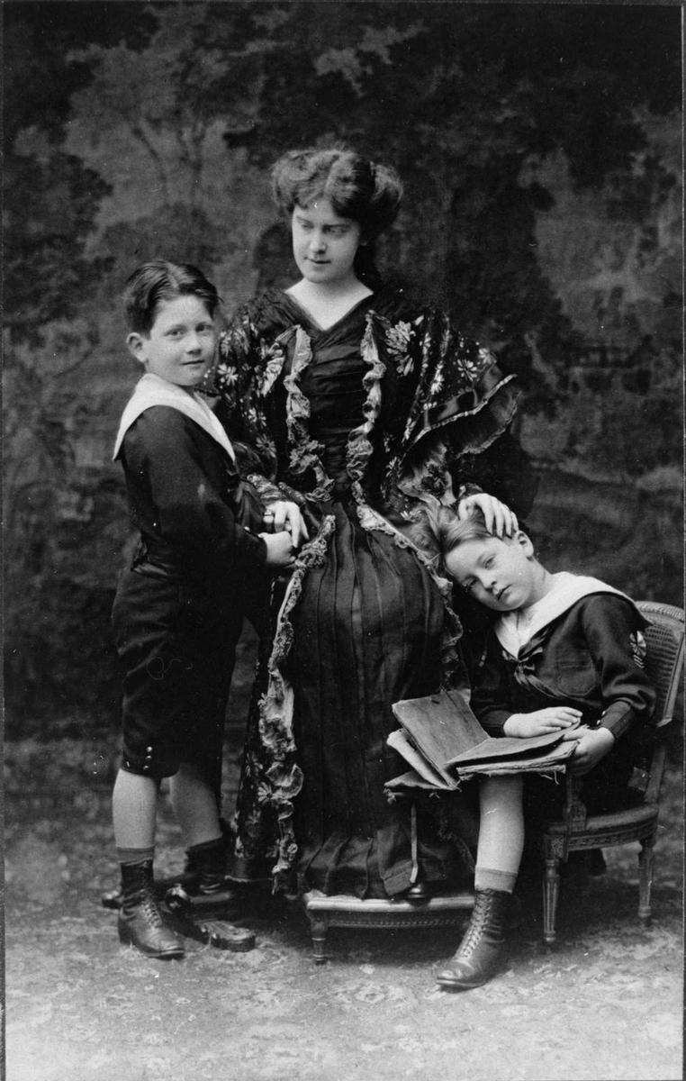 Kvinne i lang mørk kjole med to små gutter ved siden. Bildet er tatt i fotoatelier.