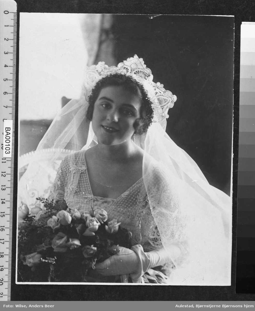 Brudebilde av bruden med kniplingdiadem og slør, brudebukett og lange hvite silkehansker og litt utskåret halsåpning i brudekjolen av tynt fint materiale med broderier. Nærbilde.