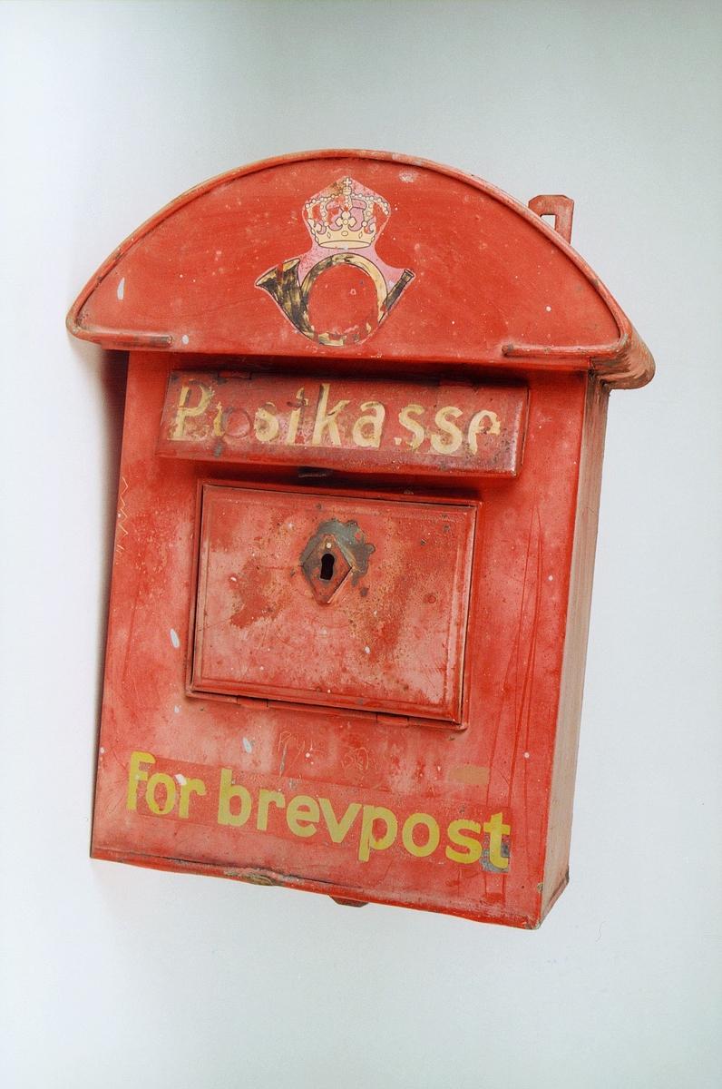 Rød postkasse med gul skrift.