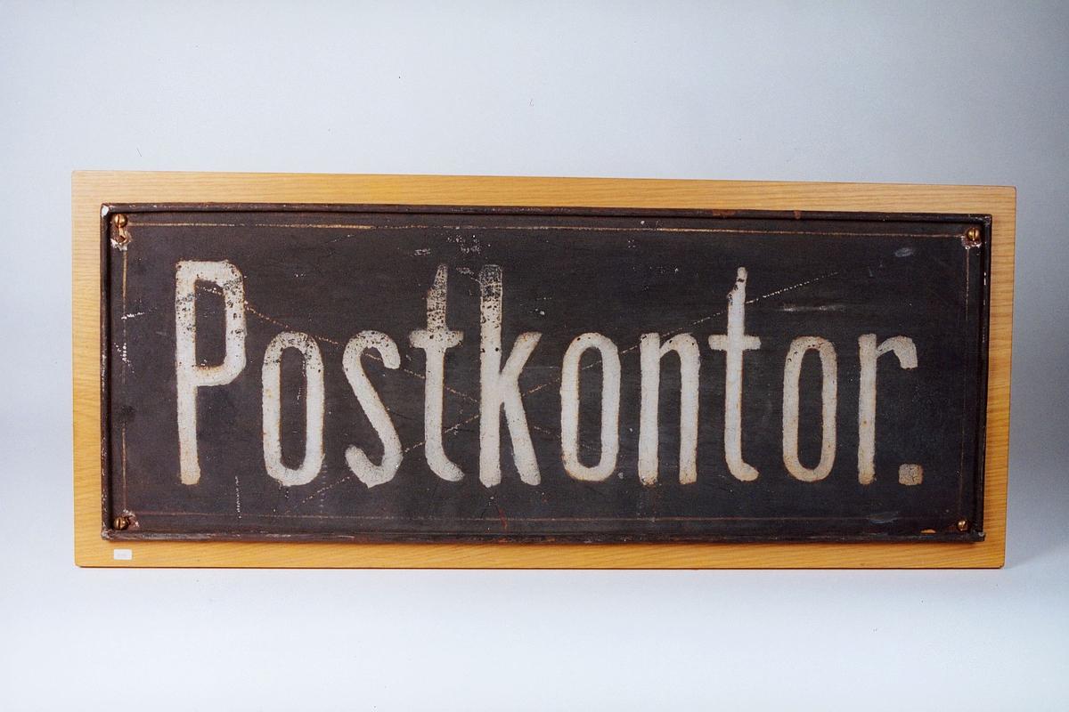 """Tekst: """"Postkontor"""". Hvit skrift på hvit bunn. Festet til en treplate"""
