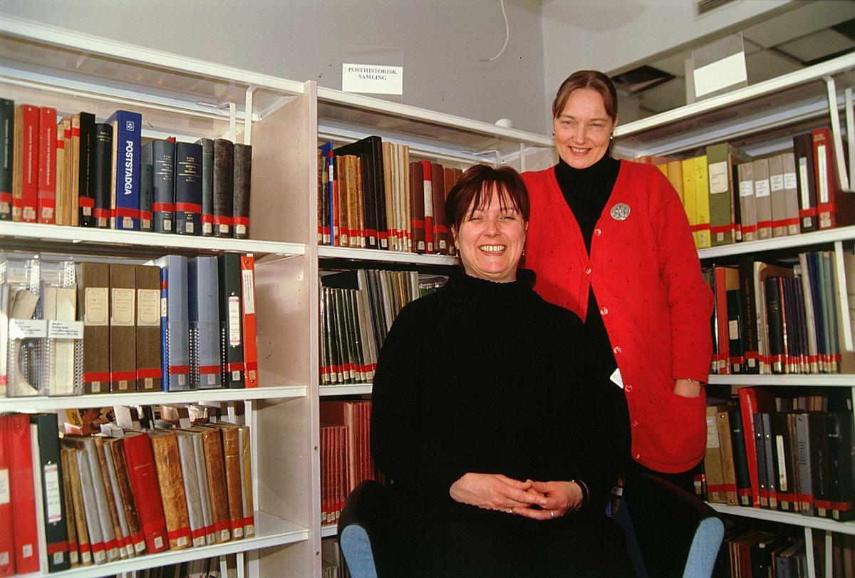 postmuseet, Kirkegata 20, biblioteket, Elin Eskerud sitter og Torgunn Haugaard står foran bokhyllene