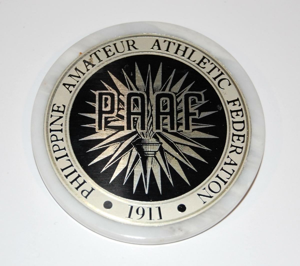 Hvit-, sort- og sølvfarget medalje av en type stenyøy- På medaljen er det logo for PAAF (Philippine Athletic Federation). I logoen inngår det en fakkel.