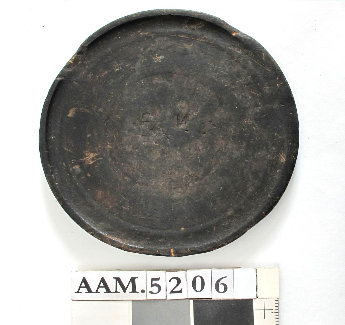"""Furu.  Flat rund tallerken med to dreieringer og en svakt opphøyd karm, som  delvis  er avslitt. Sorte (brukt i røykstove). Like på begge sider.  På den ene side risset inn   X  med kniv, på den annen side: """" Tilstand: avslitt i kanten"""
