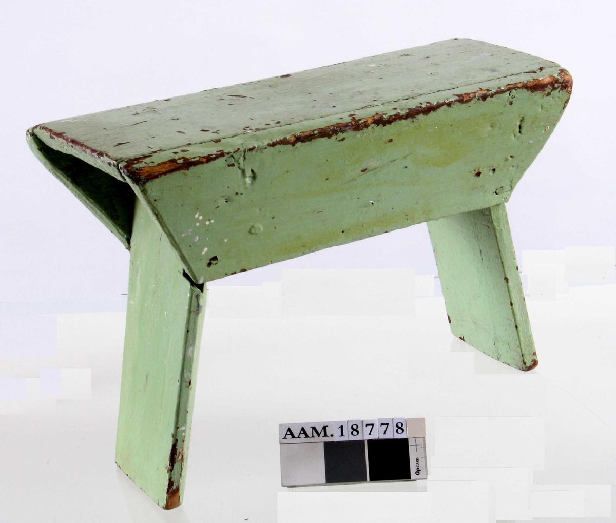 Krakk,  fra siste halvdel 1800-årene.    Furu,   malt lys grønn. Under er den malt rødbrun.   Smal, ustø krakk,   laget av grove bord.  To skråttstilte sidebord, to brede, innoverskrånede sargbord.  Tilstand: grønnmalingen avflekket til dels.