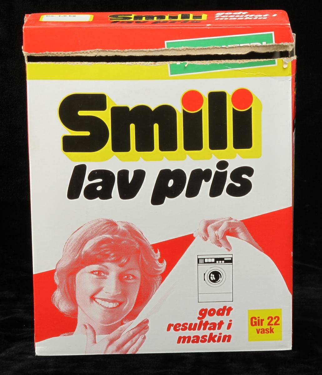 Smilende husmor holder opp hvitt tøy. Vaskemaskin.