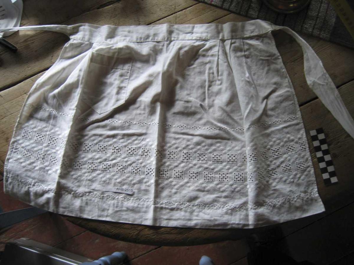 Lite forkle dekket av hardangersøm. Et fast mønster går igjen over hele forkledet. Kant av blonder. Forkle med lomme