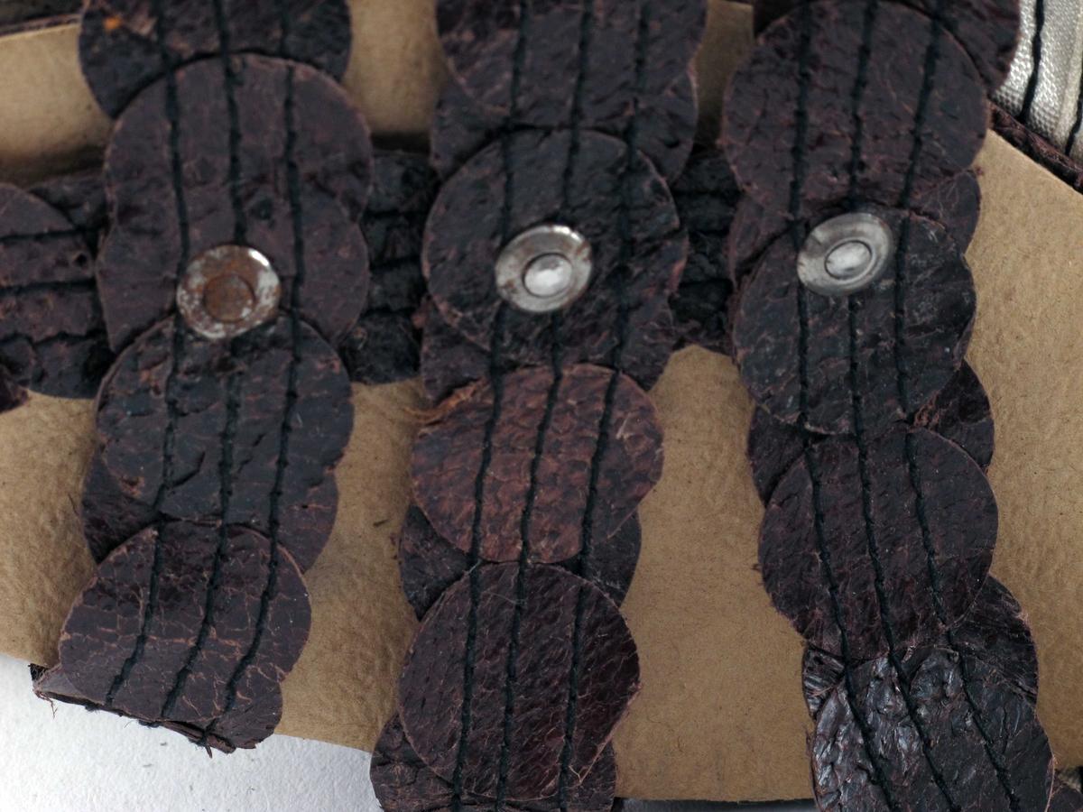 """Et par damesko av brunt fiskeskinn med lave kilehæler.    Skoene har tresåler.  Sålene har innskårne sprekker i sålen for økt fleksibilitet. Innersåle av papir og grov tekstil limt lagvis.  Brunmalt såle og hæl.   """"Overlær"""" er av sammensydde remmer i nylon med påsydde sirkler av brunt fiskeskinn: tre på tvers og en på langs over tærne, en rem med knytting over vristen og en rem bak hælen.  Knyttingen over vristen er en brun lisse.  Størrelse 38"""