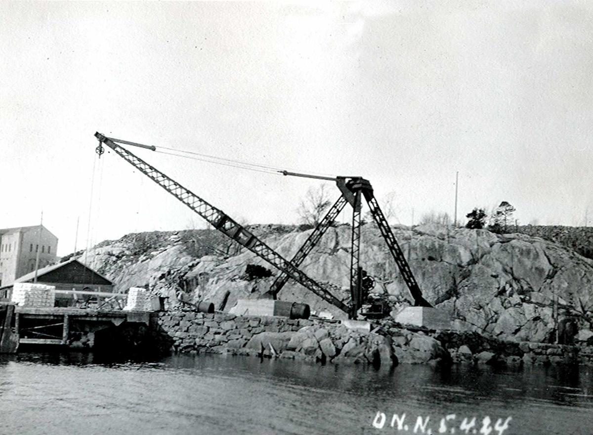 """""""05/04-1924"""" Nitriden. Montasje av kran på østre kai. Omformerstasjonen sees til venstre, og foran kaianlegget. Tromøysund i forgrunnen."""