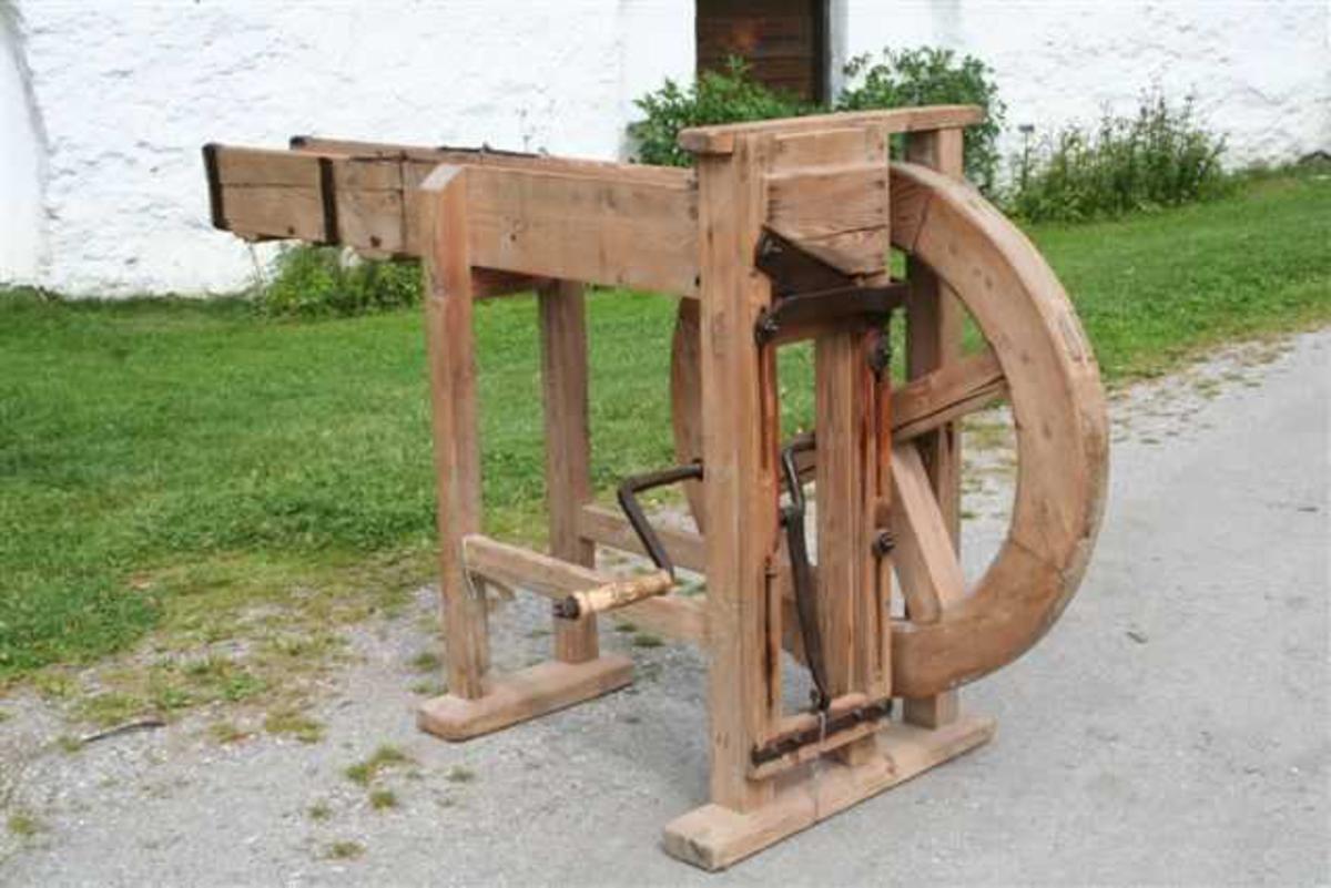 Form: Skråttstilt kniv festet i en bevegelig ramme drevet av en sveiv. Svinghjul av tre med 4 eiker i kors.