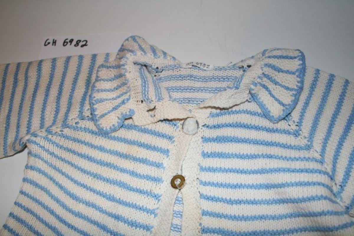 Hjemmestrikket jakke med krage til barn. Tre knapper lukker jakka. Raglandfelling rundt skulder. Glattstrikket, men regelmessige striper i vrangstrikk. Vrangbord nederst på ermer.