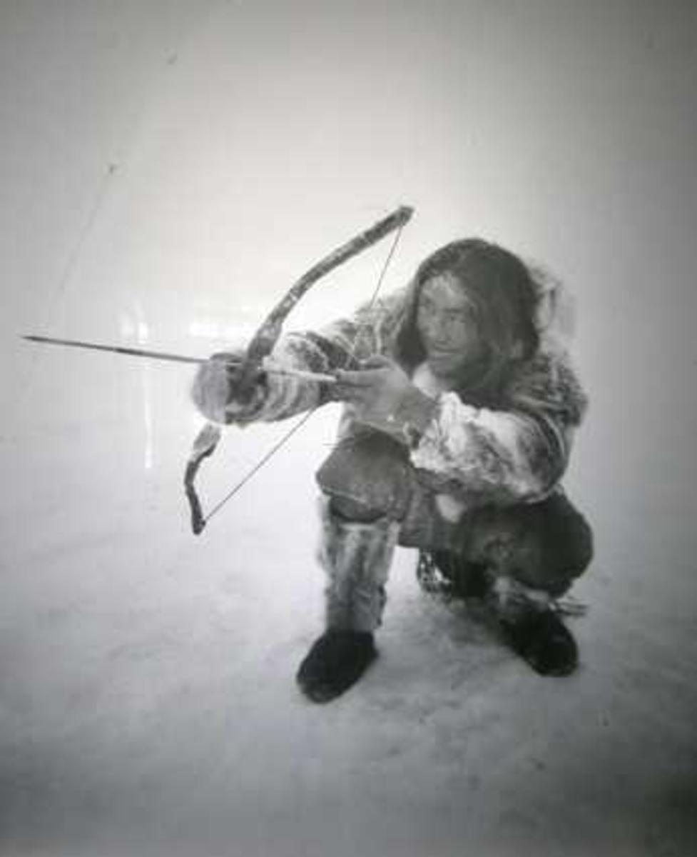 Fotografi på glassplate i dør, sort-hvitt. Viser eskimoen Ugpi med bue og pil.. Sign Worm-Petersen repro.