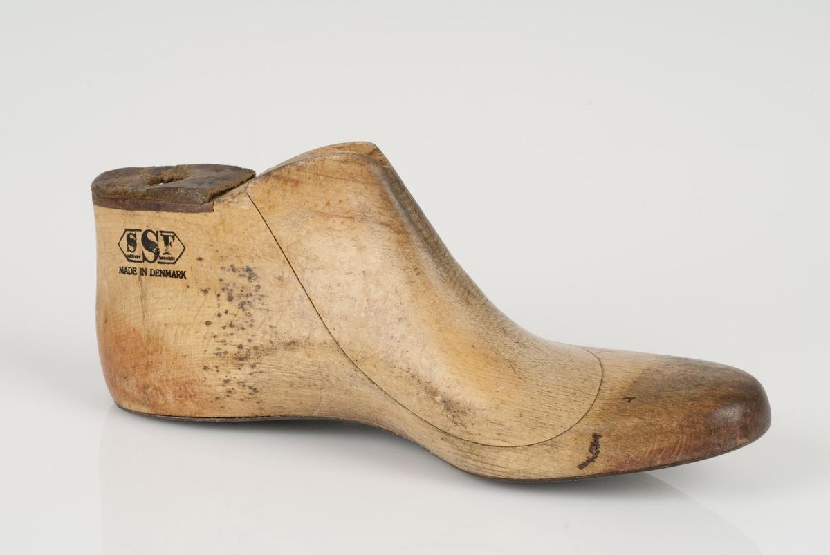 En tremodell i to deler; lest og opplest/overlest (kile). Venstrefot i skostørrelse 41. Såle av metall. Lestekam av skinn