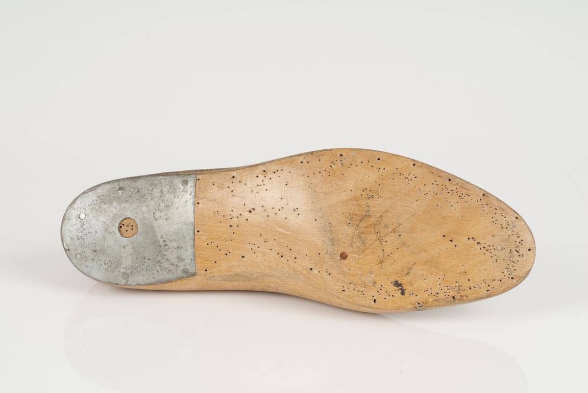 En tremodell i to deler; lest og opplest/overlest (kile) med påført tekst. Høyrefot. Lestekam av skinn. Hælstykket av metall.