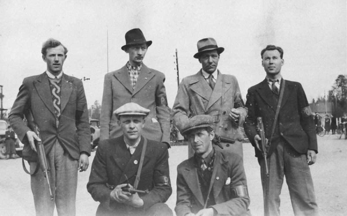 Mil.org. med våpen og armbind som indikerer at de er polititropper