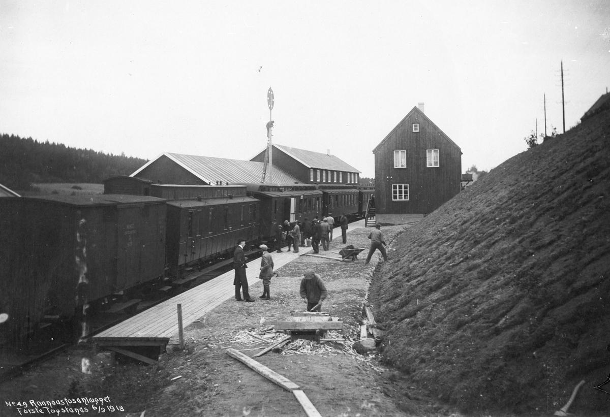 Bygging av jernbanestasjon. Stasjonshus, lokomotivstall, kombinert lastetog og persontog står på stasjonen. Personer på perrongen.