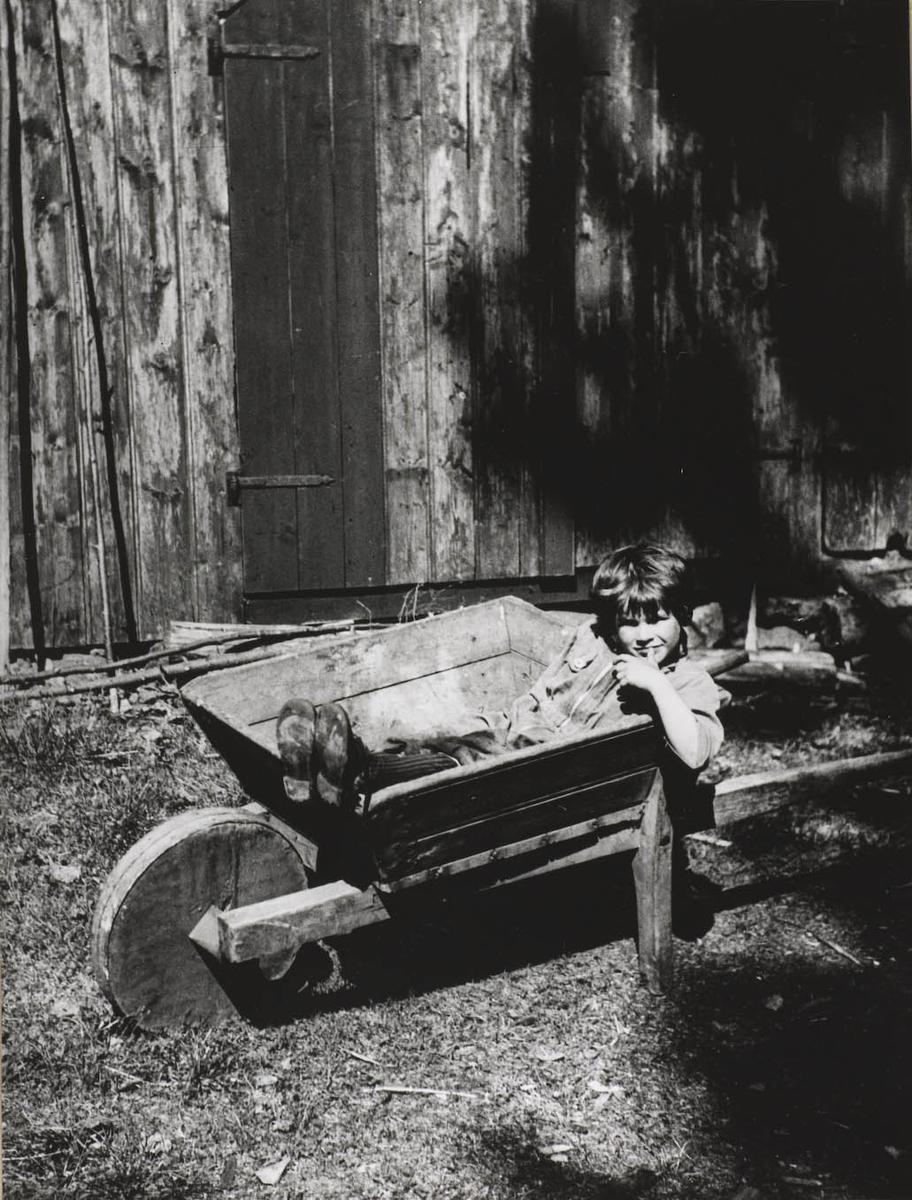 Liten gutt sittende i trillebor foran et hus.