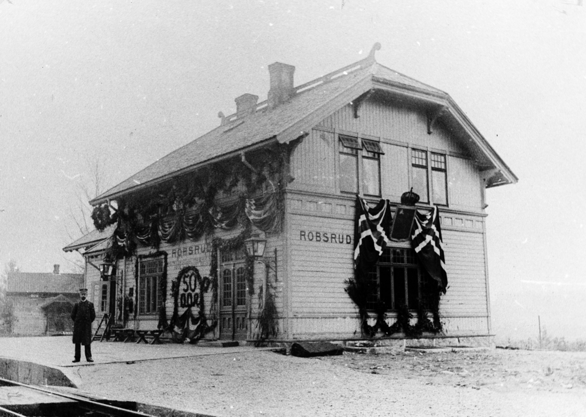 Robsrud stasjon, nåværende Lørenskog stasjon, pyntet med norske flagg og granbar til jubileum 50 år for Hovedbanen. Stasjonsmesteren på plattformen.