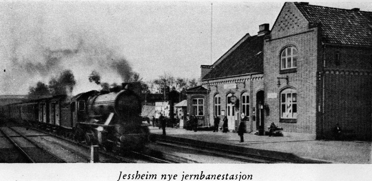 Jernbanestasjon, lokomotiv m/vogner bak, perong m/folk på