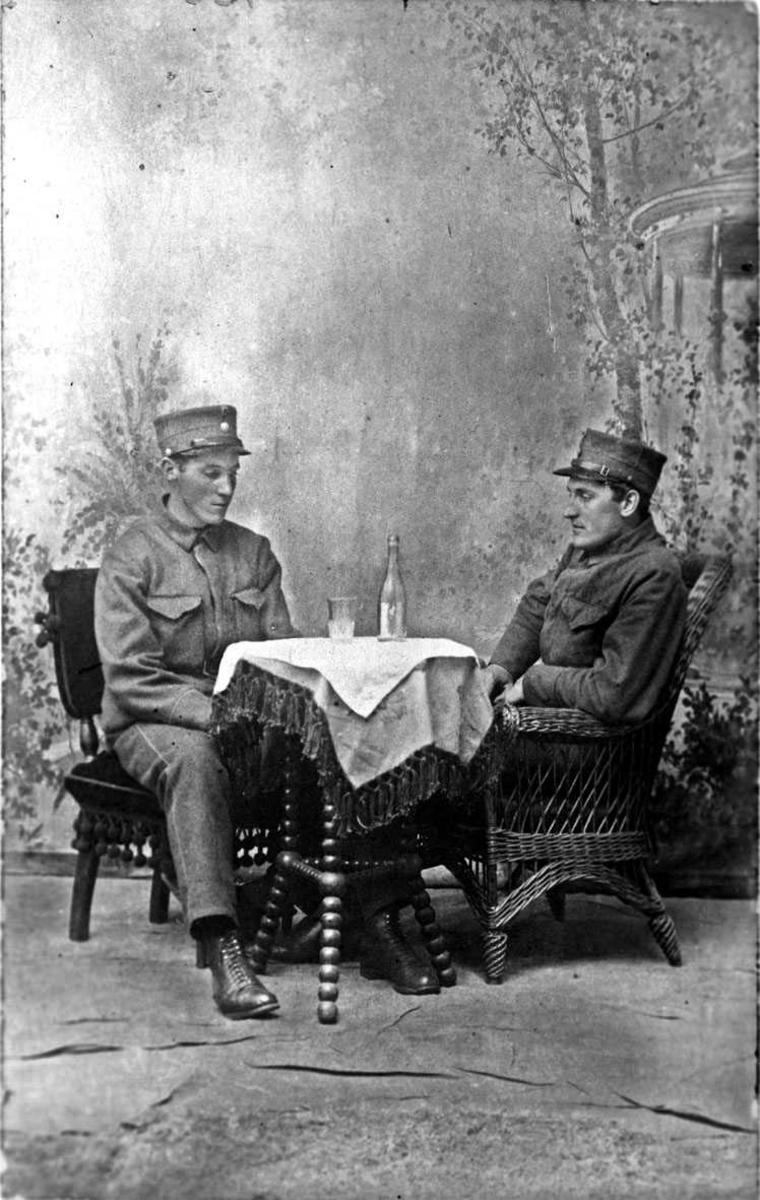 To soldater sittende ved et bord. Atelierbilde.