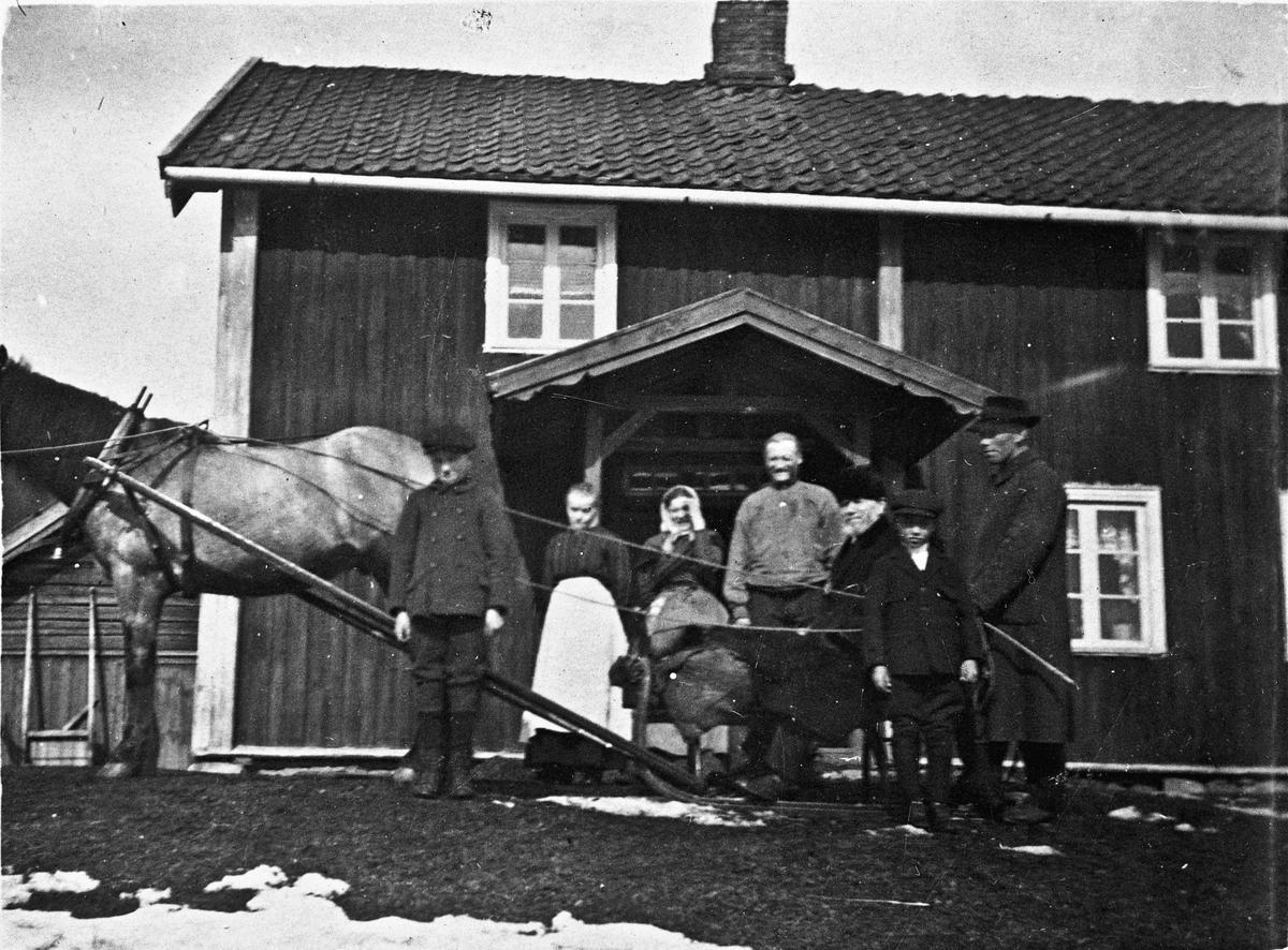 Familie med hest og slede foran hus.