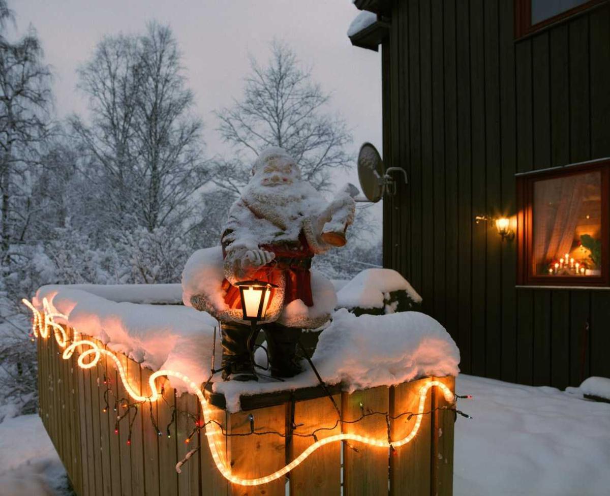 Julebelysning  Nisse med lykt og hvit lysslange og flerfarget lyslenke på veranda ved tomannsbolig