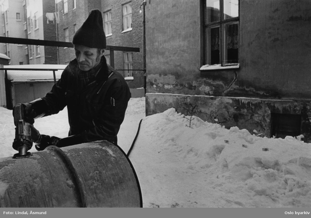 Mann som fyller på parafintønner vinterstid. Fotografiet er fra prosjektet og boka ''Oslo-bilder. En fotografisk dokumentasjon av bo og leveforhold i 1981 - 82''. Kontakt Samfoto ved ev. bestilling av kopier.