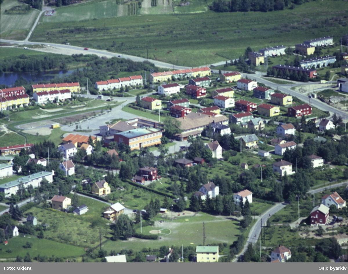 Abildsø skole midt på bildet, Enebakkveien foran. Rekkehusene i Svaneveien og Grågåsveien bak. Abildsøveien helt i front. Østensjøveien går gjennom bildet. (Flyfoto)