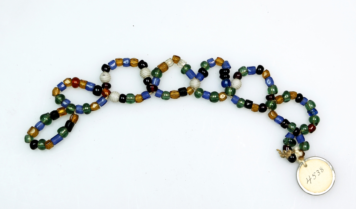 Perler i ulike farger og utforming tredd på snorer, som er tvunnet og knytt i mønster