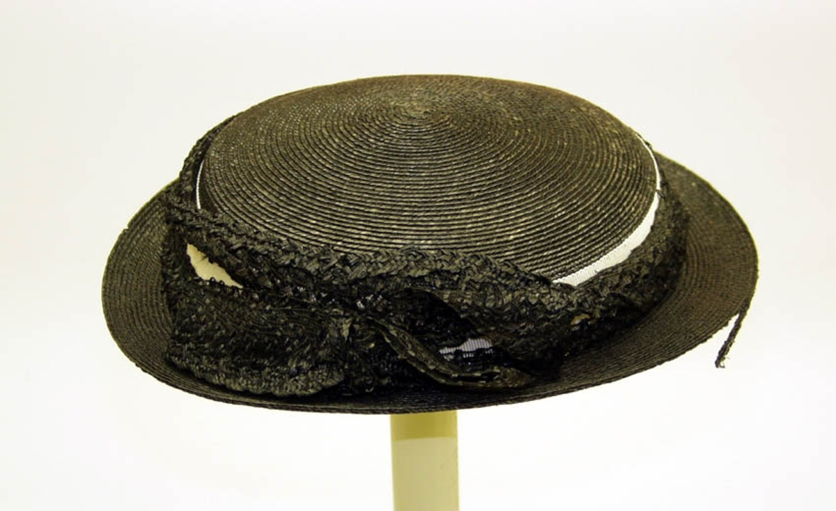 Hatten har hcitt ripsbånd dekket med transparent bånd, ender i sløyfe. Samme bånd rundt hatten, løst ripsbånd, hattestrikk inne i hatten.