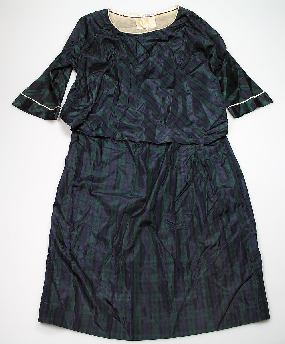 Kjole.  Skjørt og overdel, søm i livet, stor vidde foran.  Rund hals, med hvit kant med trekkbånd. Kimono form med isydd erme.