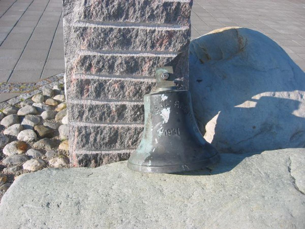 Minnebauta med inskripsjon. Ved foten av bautaen skipsklokken.
