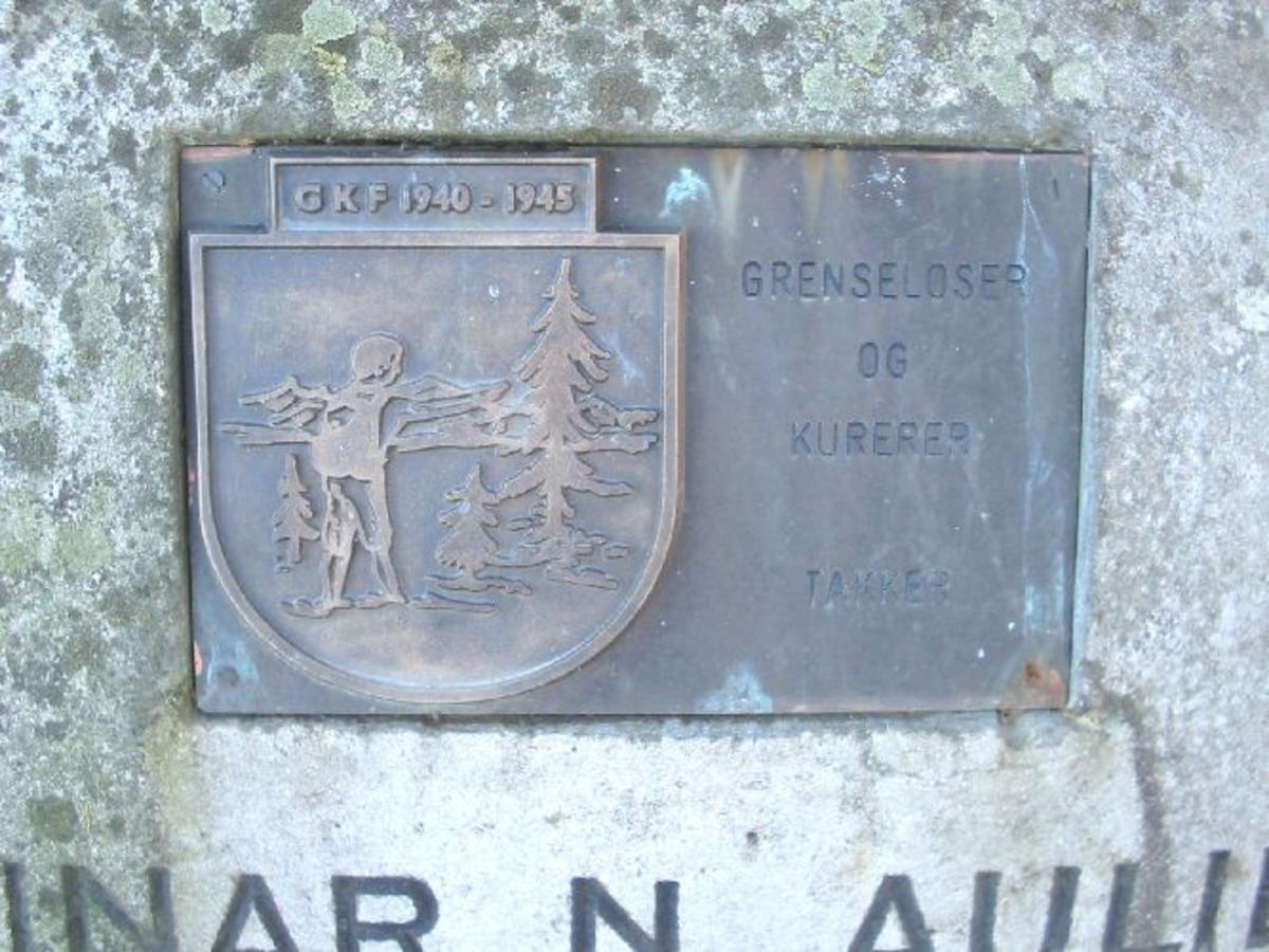 """En kobberplate med GKFs merke og følgende inskripsjon er festet på gravmonumentet: """"GKF 1940-1945 Grenseloser og kurerer takker"""""""