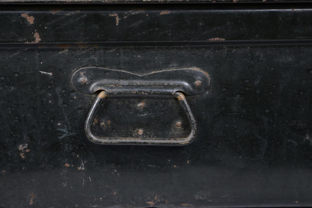 Avlang, relativt lav kiste av metall. Tre håndtak, en på hver kortside og en på låsesiden. To låsemekanismer uten lås. Tre langsgående forsterkninger på det hengslede lokket. Ekstra forsterkninger på hjørnene, hjørnene er avrundede. Rest etter pålimt papirlapp. Innvendig er kisten et åpent rom, grønnlakkert.