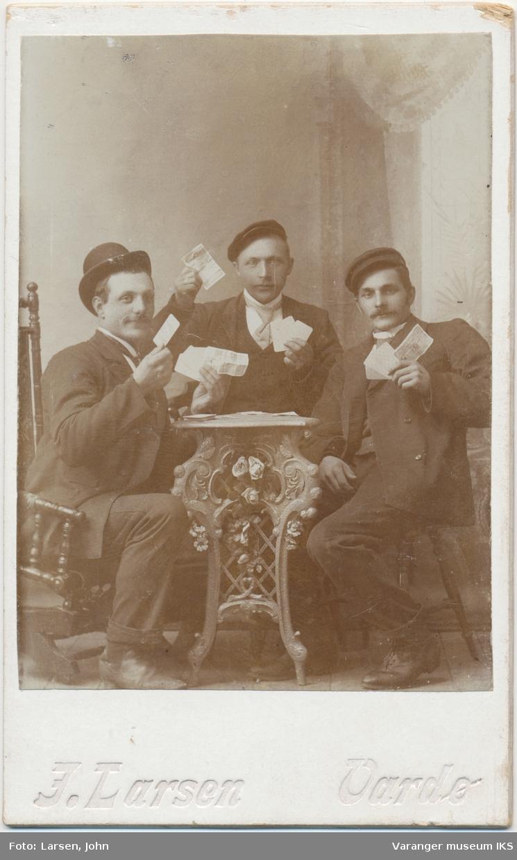 Gruppeportrett, tre menn poserer med kort og pengesedler