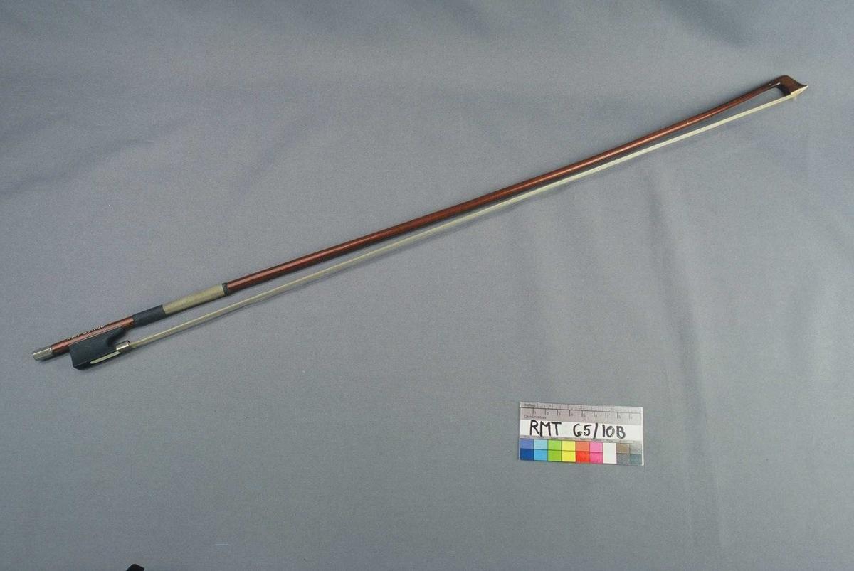 Bue av rødlakkert tre. Ibenholtfrosch, skyver av ben. 6-kantet metallskrue. Nedre del omviklet med sort og beige impregnert bånd.