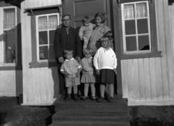 Familie på trappa ved inngangen til et hus.  Bildet er tatt
