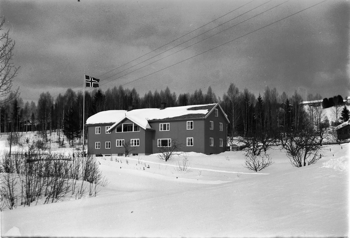 Eksteriør, vinter. Ukjent hus som flagger med det norske flagget.