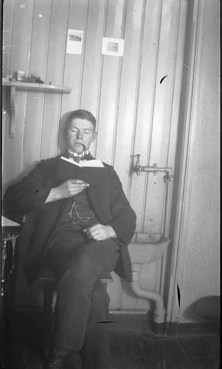 Interiør, med utslagsvask. Ukjent gutt med pipe leser en bok.