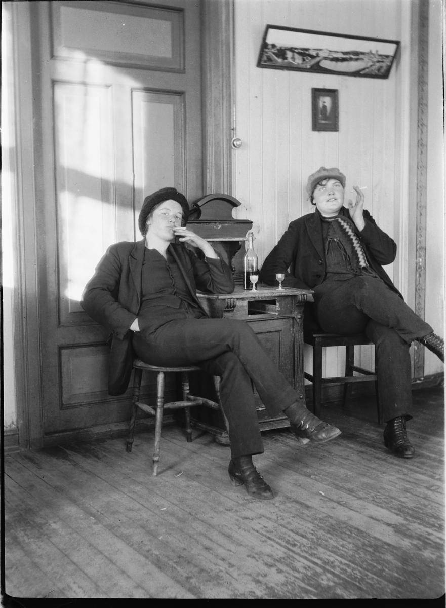 Interiør, stue. To kvinner røyker og tar seg en dram.