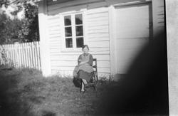Ei kvinne sitter på en stol ved inngangsdøra til et hus.